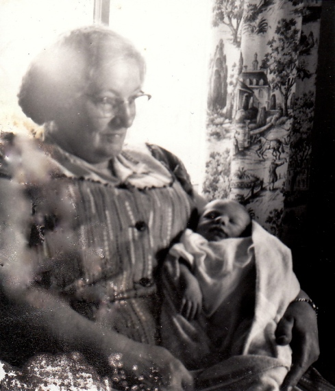 Old and regrettably damaged photo of Grandma Benson holding baby me